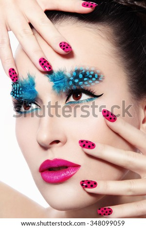 Close-up portrait of young beautiful woman with fancy feather eyebrows and dot manicure