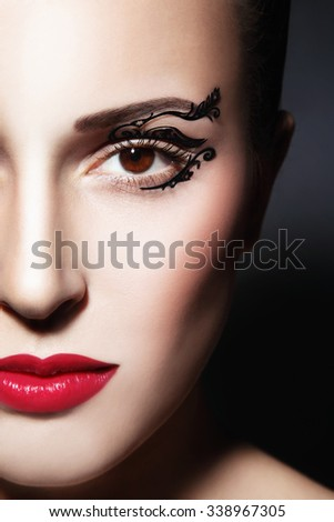 Close-up portrait of young beautiful woman with fancy paper eye stickers - stock photo