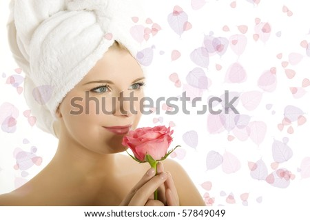 close-up portrait of Young beautiful woman with healthy pure skin and wet hair in a towel holding pink rose flower. - stock photo