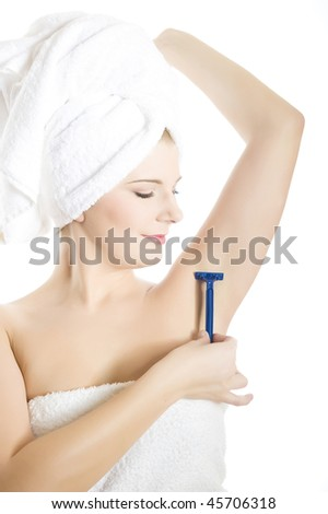 close-up portrait of Young beautiful woman with healthy pure skin and wet hair in a towel holding a razor blade preparing to shave an armpit. isolated on white background. copy-space - stock photo