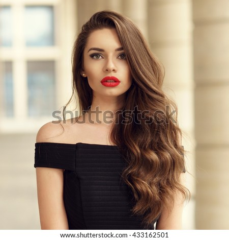 Close up portrait of young beautiful woman with long brunette curly hair posing against architectural background and looking at you - stock photo