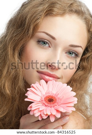 Close-up portrait of young beautiful woman with long curly hair holding pink flower. Isolated on white background - stock photo
