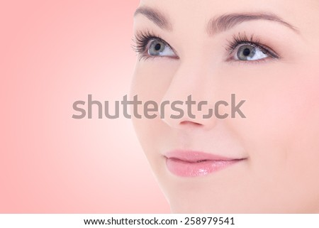 close up portrait of young beautiful woman with long eyelashes over beige background - stock photo