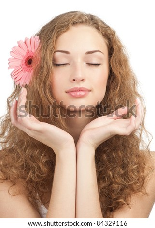 Close-up portrait of young beautiful woman with pink flower in her hair holding her hands near the face. Isolated on white background - stock photo