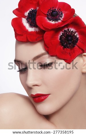 Close-up portrait of young beautiful woman with red flowers in her hair - stock photo