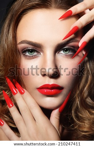 Close-up portrait of young beautiful woman with red lipstick and long stiletto nails - stock photo
