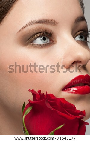 Close-up portrait of young beautiful woman with red rose and stylish bright make-up