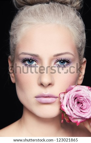 Close-up portrait of young beautiful woman with rose - stock photo