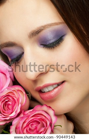 Close-up portrait of young beautiful woman with roses and stylish make-up