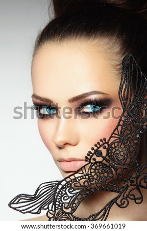 Close-up portrait of young beautiful woman with smoky eyes and lacy black mask - stock photo