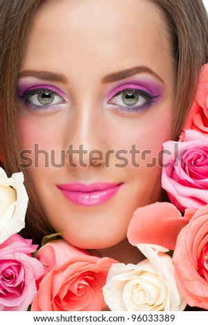 Close-up portrait of young beautiful woman with stylish bright make-up surrounded by roses