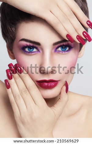 Close-up portrait of young beautiful woman with stylish make-up and long nails