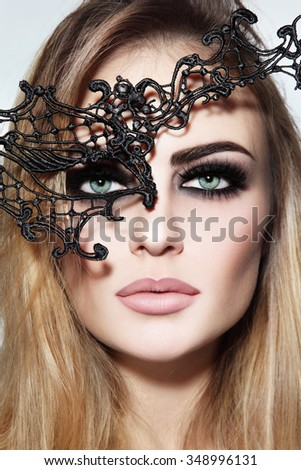 Close-up portrait of young beautiful woman with stylish smoky eyes and black lacy mask - stock photo