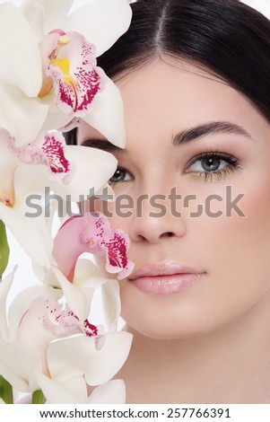 Close-up portrait of young beautiful woman with white orchid - stock photo