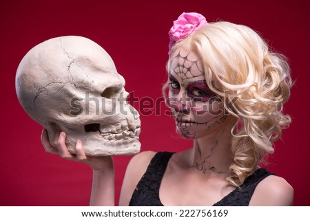 Close-up portrait of young blond girl with sad face with Calaveras makeup and a rose flower in her hair curiously looking at the camera while holding a skull isolated on red background with copy place - stock photo