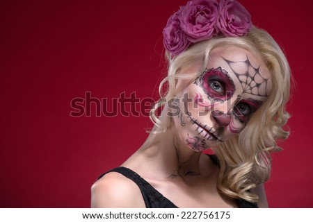 Close-up portrait of young blond girl with sad face with Calaveras makeup and a rose flower in her hair curiously looking at the camera isolated on red background with copy place - stock photo