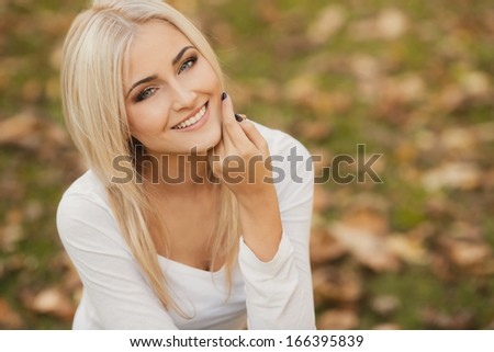 Close up portrait of young blonde beautiful woman in warm autumn scarf. Ourdoors. - stock photo