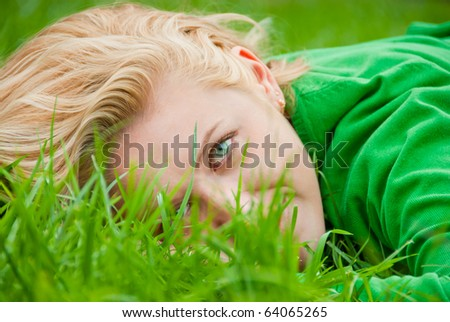 Close-up portrait of young blonde lying in a grass - stock photo