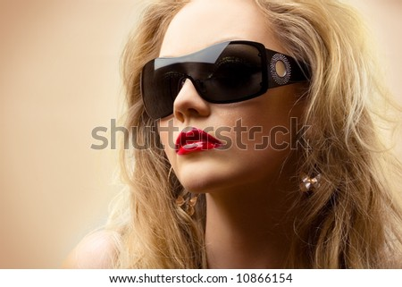 close-up portrait of young blonde wearing stylish sunglasses - stock photo