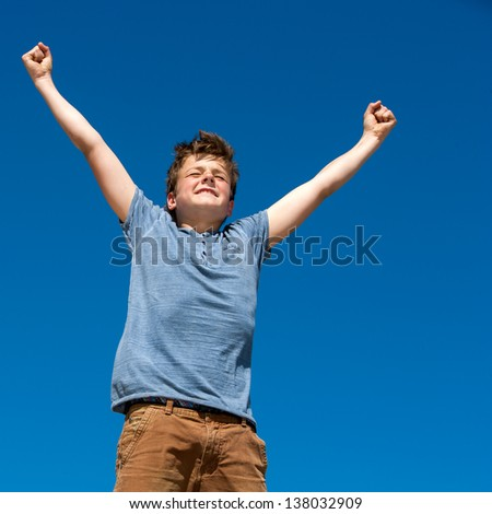 Close up portrait of young boy with open arms outdoors. - stock photo