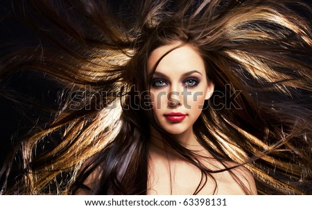 close up portrait of young brunette woman, with her hair in motion