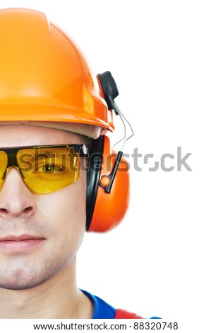 close-up Portrait of young builder in protective safety equipment goggles hard hat earmuffs isolated - stock photo
