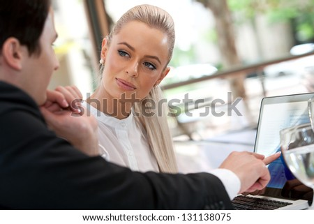 Close up portrait of young business colleagues reviewing work at lunch. - stock photo
