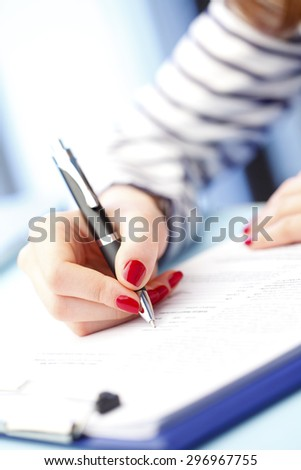 Close-up portrait of young businesswoman sitting at desk and signs the contract.  - stock photo