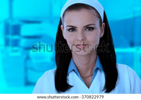 Close-up portrait of young caucasian female nurse in blue lit medical scanner room. - stock photo