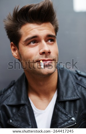 Close up portrait of young charming man with cigarette in his mouth standing on grey background, attractive young man friendly looking up while smoking the cigarette - stock photo