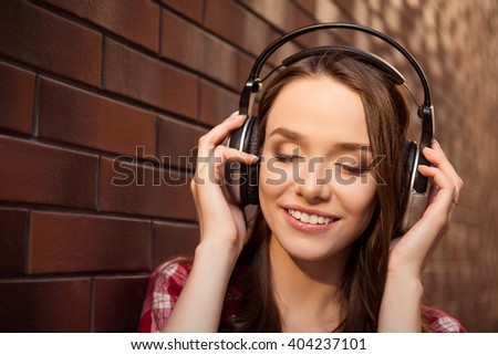 Close up portrait of young cheerful girl listening music with headphones - stock photo