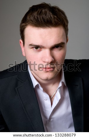 Close-up portrait of young confident businessman on a gray background - stock photo