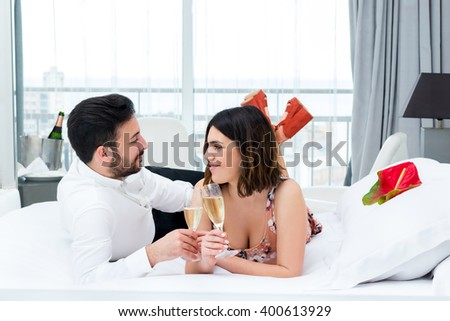 Close up portrait of young couple on honeymoon in hotel.Man and woman drinking champagne on bed in suite.