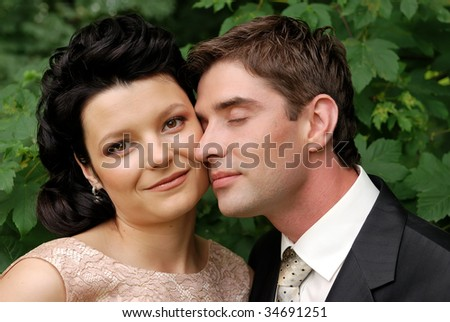 Close-up portrait of young couple outdoors. Man tenderly nestled up to the woman cheek. - stock photo