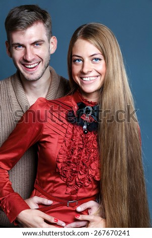 Close up portrait of young couple over dark gray background - stock photo