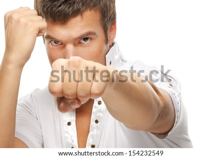 Close-up portrait of young dark-haired man holding fists in front of his face against white background. - stock photo
