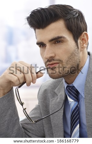 Close-up portrait of young daydreaming businessman, looking away, holding glasses in hand. - stock photo