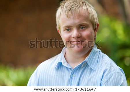 Close up portrait of young disabled man outdoors. - stock photo