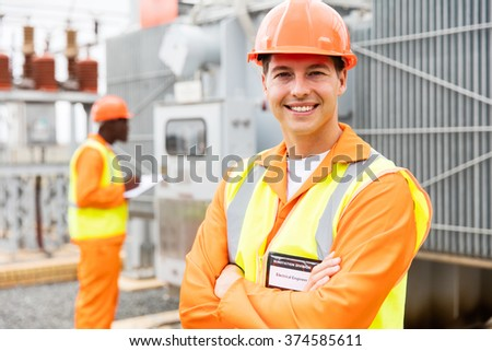 close up portrait of young electrical engineer with arms crossed in substation - stock photo