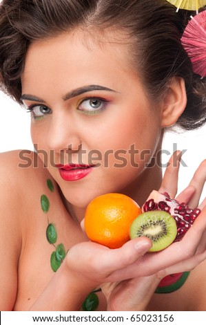 Close up portrait of young emotional beauty woman with piece of garnet, kiwi and orange. Perfect skin! Isolated on white.