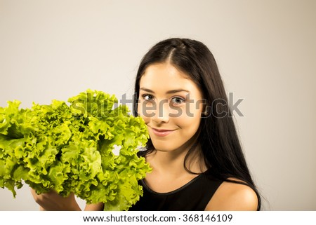 Close up portrait of young emotional woman . Beautiful healthy girl with lettuce - stock photo