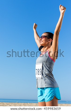 Close up portrait of young female athlete with start number showing winning attitude.Girl raising arms at sea front.