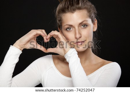 Close-up portrait of young female forming heart shape with her hands looking at the camera - stock photo
