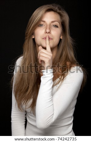 Close-up portrait of young female looking at the camera with finger on lips isolated on black background - stock photo