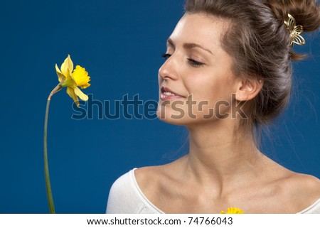 Close-up portrait of young female looking at the flower isolated on blue background - stock photo