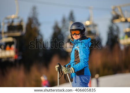 Close-up portrait of young female skier against ski-lift on a sunny day. Woman is wearing helmet skiing glasses gloves and blue ski suit. Ski resort at Carpathian Mountains, Bukovel, Ukraine - stock photo