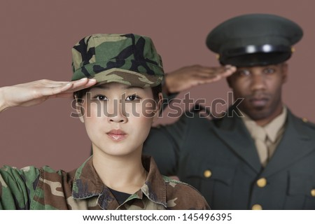 Close-up portrait of young female US Marine Corps soldier with male officer saluting over brown background - stock photo