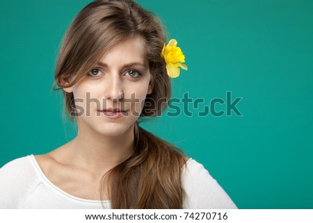 Close-up portrait of young female with flower over the ear on turquoise background - stock photo