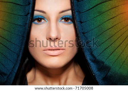 Close-up portrait of young female with make-up and conventionalized rainbow wings - stock photo