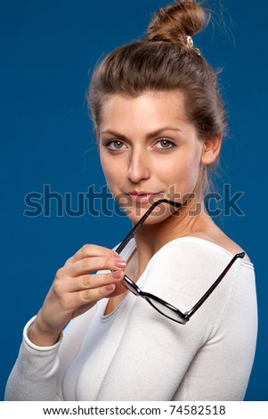 Close-up portrait of young femaleholding old fashioned eyeglasses looking at the camera - stock photo